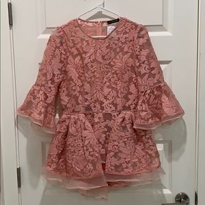 Peplum top with back zipper and bell sleeves.